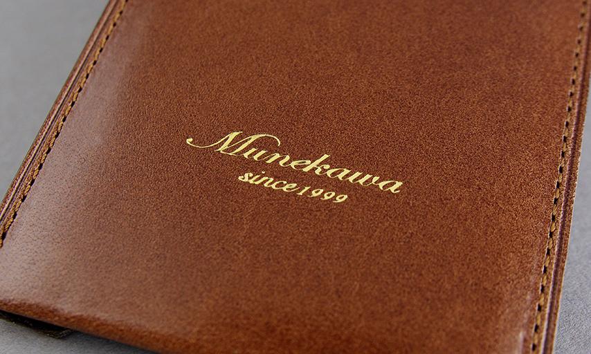 表にはMunekawaの刻印。ゴールドの箔押しでエレガントさを演出する。<br>
