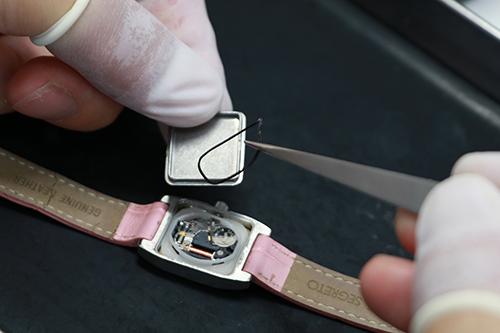 手作業で腕時計のネジを外しています